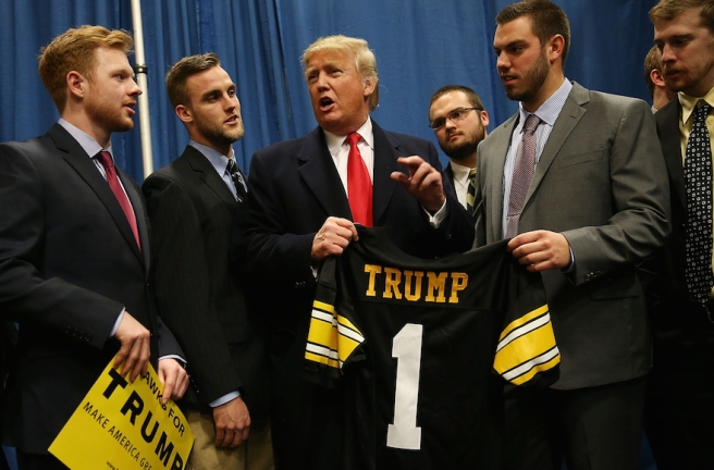 IOWA CITY, IA - JANUARY 26:  Republican presidential candidate Donald Trump stands with football players from the University of Iowa as they present him with a football jersey during a campaign event at the University of Iowa on January 26, 2016 in Iowa City, Iowa. Trump continues his quest to become the Republican presidential nominee.  (Photo by Joe Raedle/Getty Images)